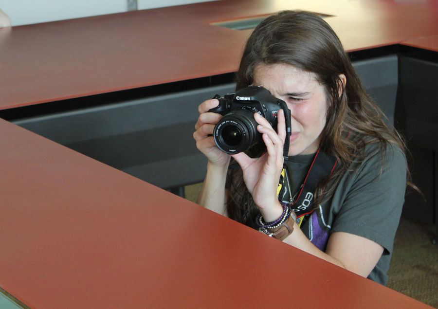 Mentor, Maggie Pund finds herself in the middle of the conference table to snap some photos of the students during Dean Hume's presentation.