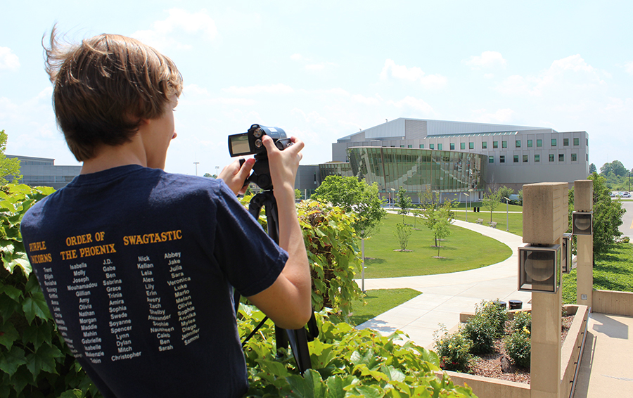 Joseph Glandorf shoots video with his tripod outside of Founder Hall of Griffin Hall.