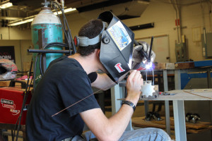 Nathan Rogers, president of the SAE Baja club, welds a piece for the buggy they built.  Photo by Maggie Pund.