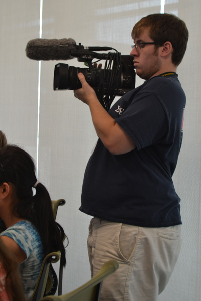 Video Editor and mentor Brian Murray films while an instructor teaches the students.