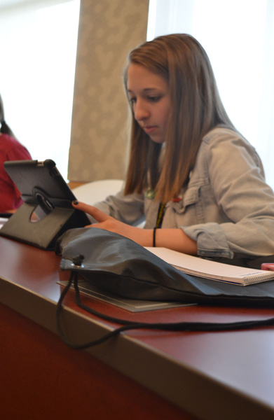 Brianna Jones researches Coach Plitzuneit and the NKU Women's Basketball team before the press conference.