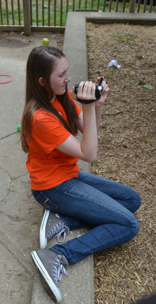Hannah Brandell sits as she photographs children at the daycare.