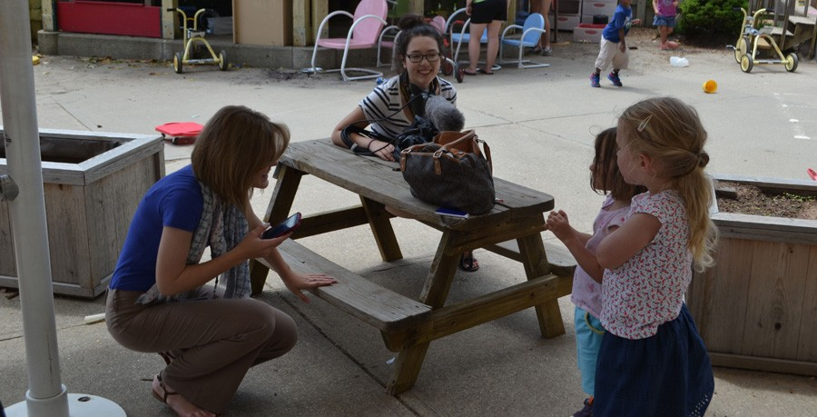 Mentors Taylor Upchurch and Lindsey Rudd take a break to chat with some children at the daycare.
