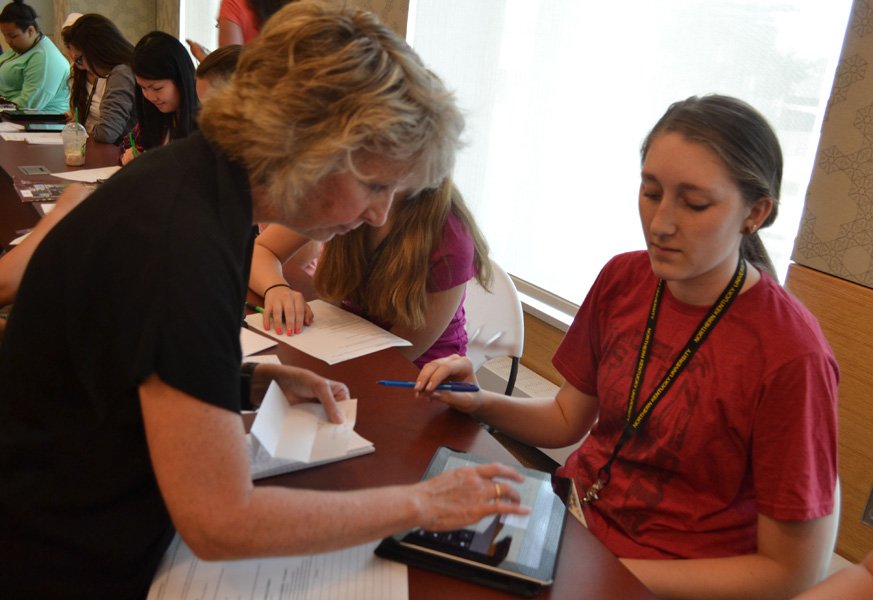 Michelle Day helps Hannah Brandell with her iPad.