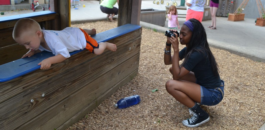 Whitney Bronson photographs a climbing child at the daycare.