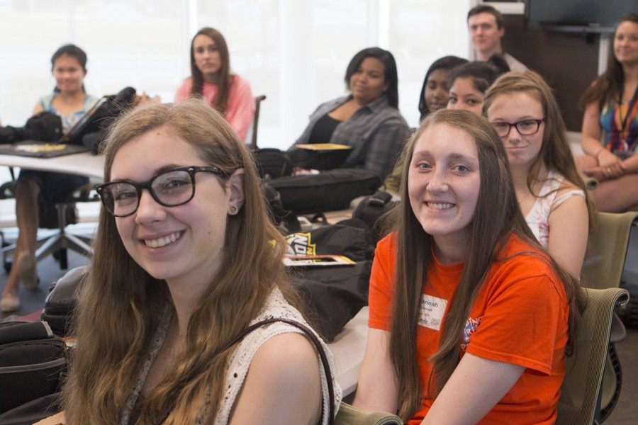 Elizabeth Juengling, Hannah Brandell, and Savannah Deuer smile for the camera while instructor teaches them about the art of photo journalism.