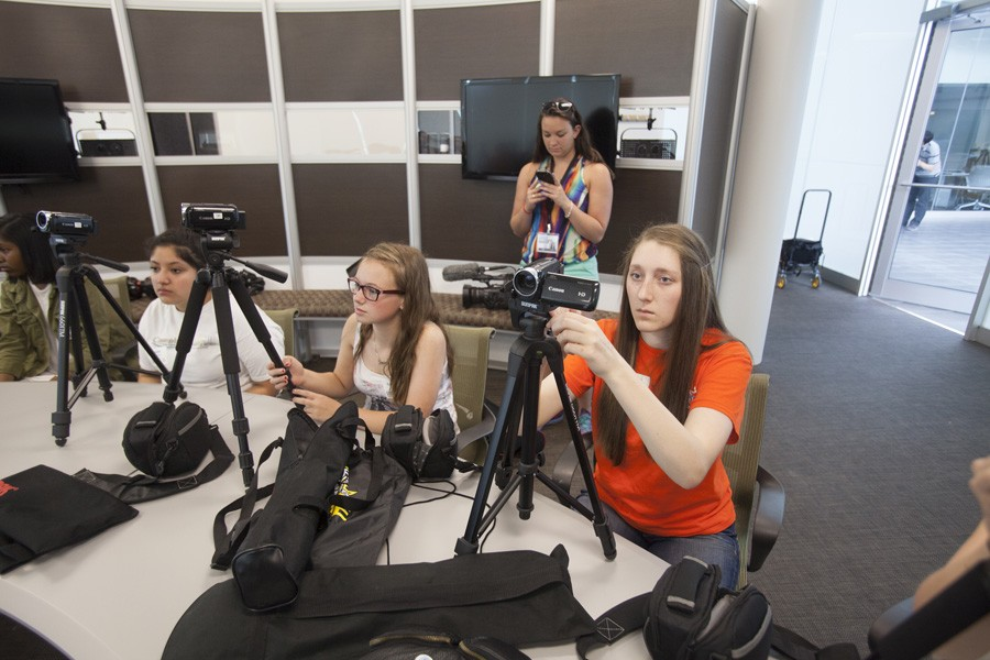 Natalie Hempfling, Savannah Deuer, and Hannah Brandell gets hands on instructions on how to use the cameras.