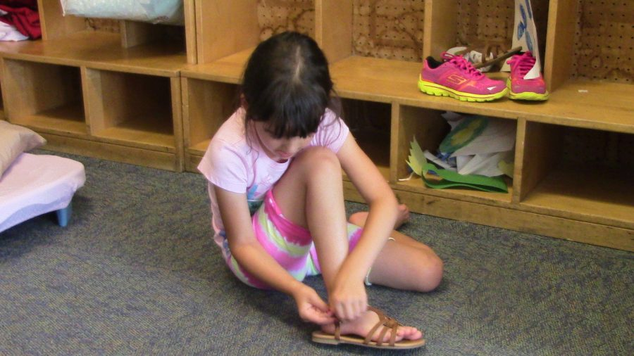 A girl putting on her shoes