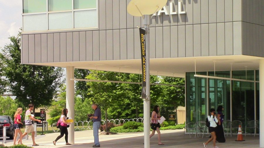 Students from NKU's digital journalism workshop walk around Griffin Hall taking pictures.