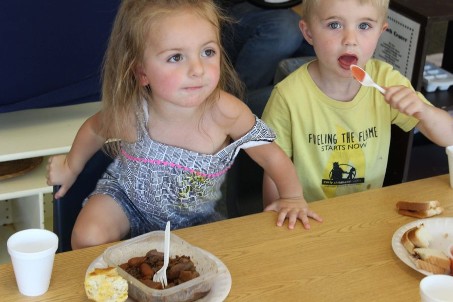 Cooper moves his spoon of applesauce over to his mouth, while Autumn tried to get out of her seat.