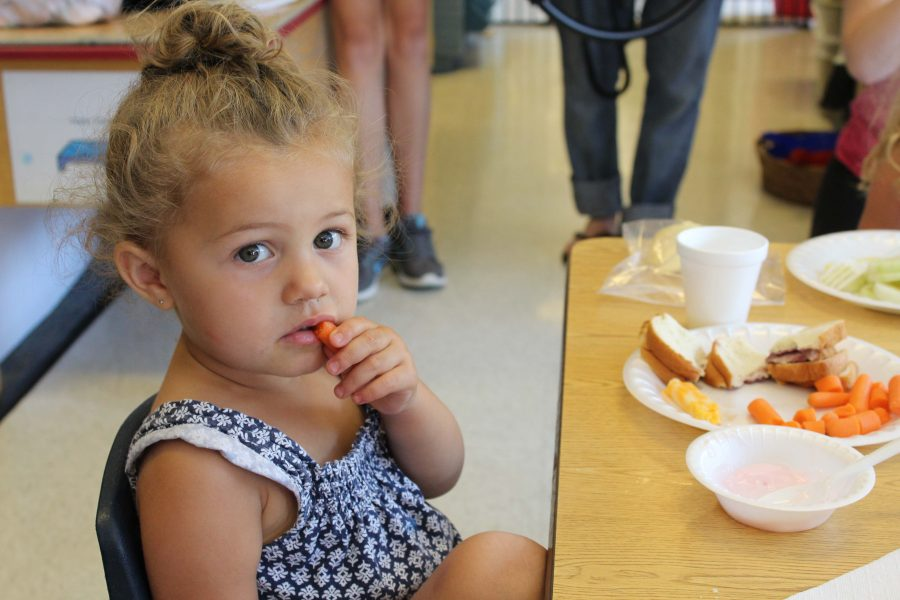 Mia, two-years-old, enjoys her lunch at the NKU daycare.