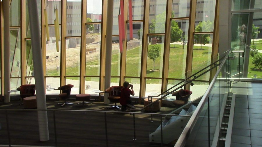 A student taking a photo out of Griffin Hall's massive windows.