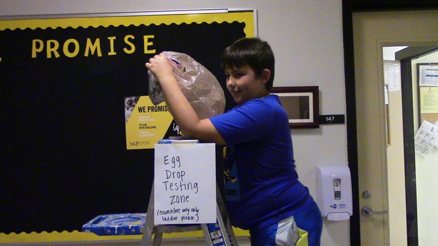 Student gets ready to test out his egg drop device.