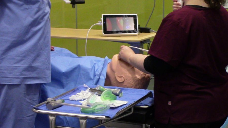 A student performs a procedure on one of the simulation dummies in the Health Informatics Center's new simulation lab.