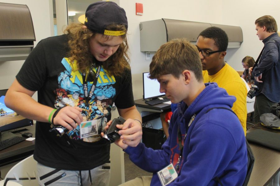 Kryton J. helps another student take photos.