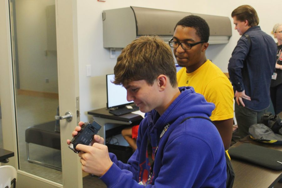 Mentor Josh Kelly helps a student operate his camera.