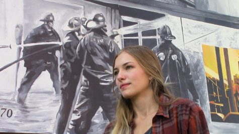 Madeline Filimonov stands in front of one of the murals at the Newport History Museum.