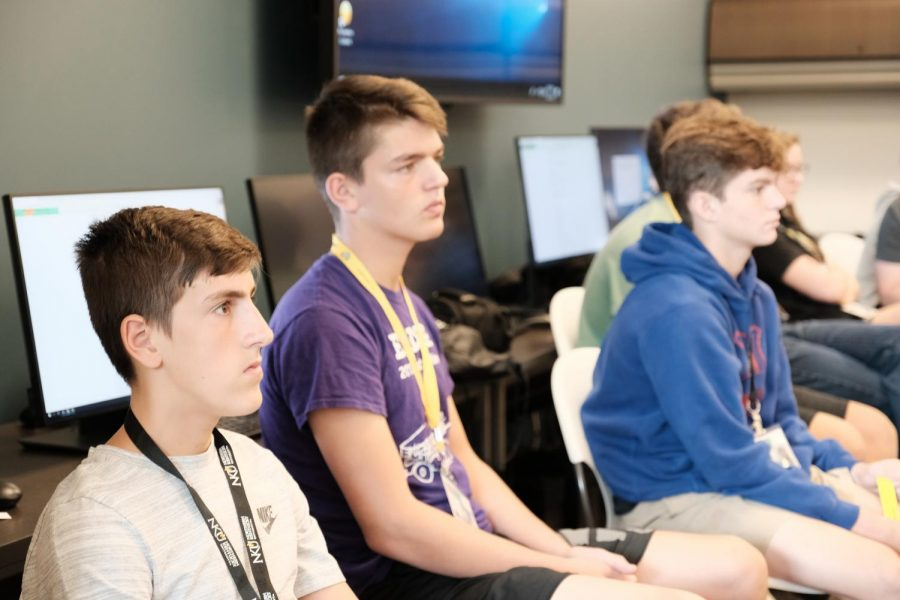 Justin G., Jack L. and Tyler G listen to Dr. Stacie Jankowskis lecture on media ethics.