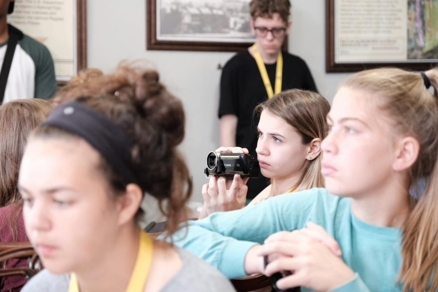 McKenzie K. films historians answer questions as other students listen in.